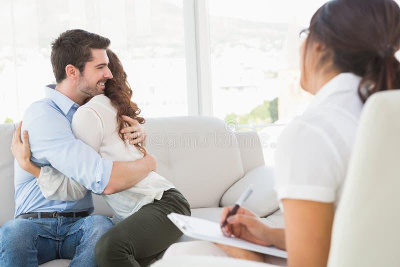 Lächelnde Paare, die vor ihrem Therapeuten umarmen stockbild