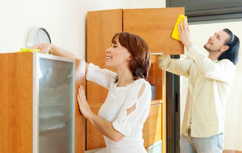 Lächelnde Paare, die zu Hause Aufgaben tun lizenzfreie stockfotografie
