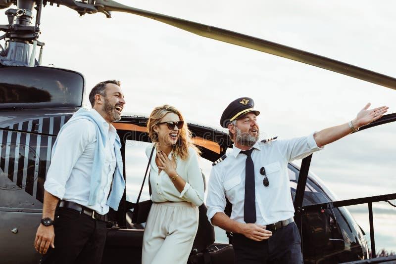 Lächelnde Paare durch einen privaten Hubschrauber mit Piloten lizenzfreies stockbild