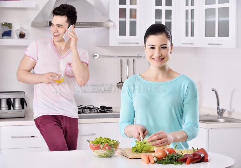 Lächelnde Paare essen Salat in der Küche lizenzfreies stockfoto
