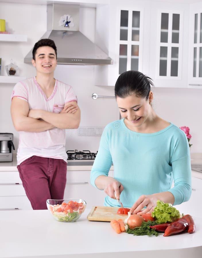 Lächelnde Paare essen Salat in der Küche stockbilder