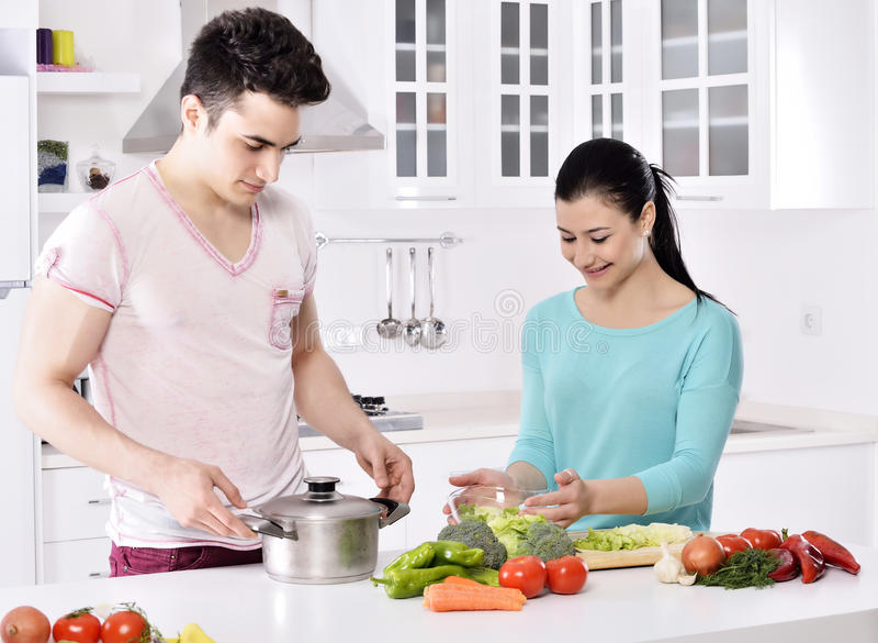 Lächelnde Paare essen Salat in der Küche lizenzfreie stockbilder