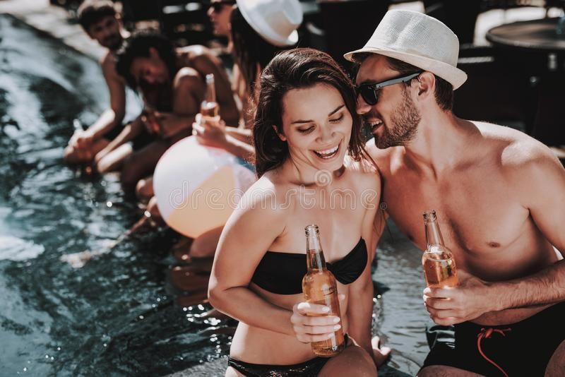 Lächelnde Paare mit alkoholischen Getränken am Poolside stockfotos