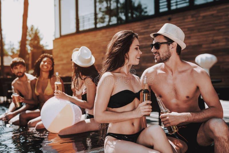 Lächelnde Paare mit alkoholischen Getränken am Poolside lizenzfreies stockfoto