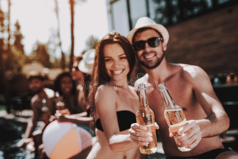 Lächelnde Paare mit alkoholischen Getränken am Poolside stockfotografie