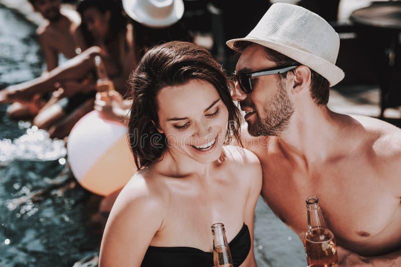 Lächelnde Paare mit alkoholischen Getränken am Poolside stockfoto