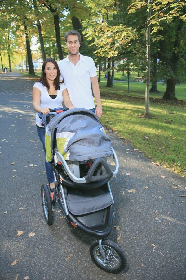 Lächelnde Paare mit Kinderwagen in einem Park lizenzfreie stockbilder