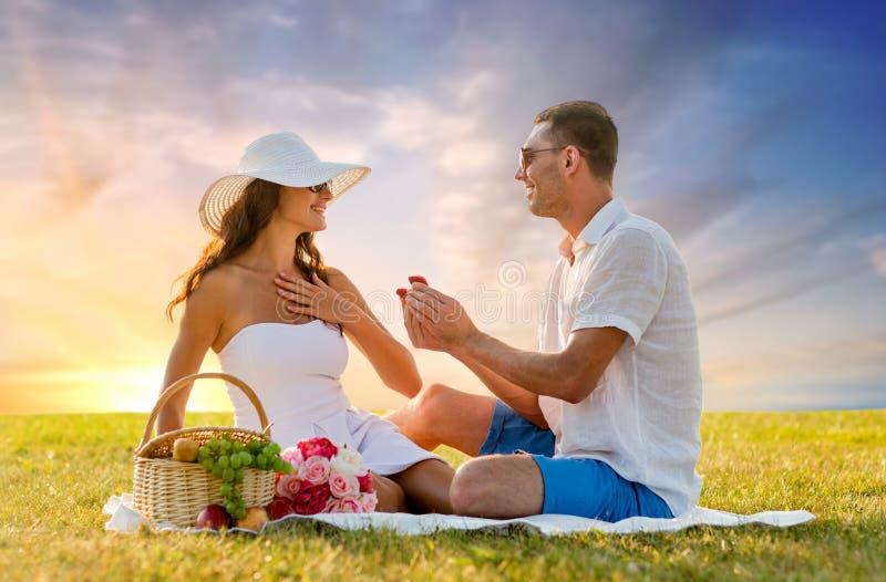 Lächelnde Paare mit kleiner roter Geschenkbox am Picknick stockfotos