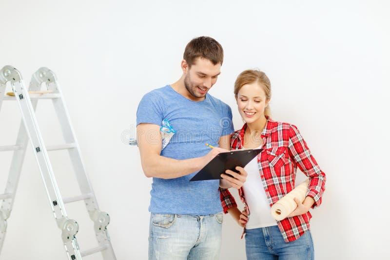Lächelnde Paare mit Klemmbrett- und Tapetenrolle stockfotografie