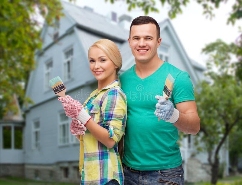 Lächelnde Paare mit Pinseln über Haus stockbilder