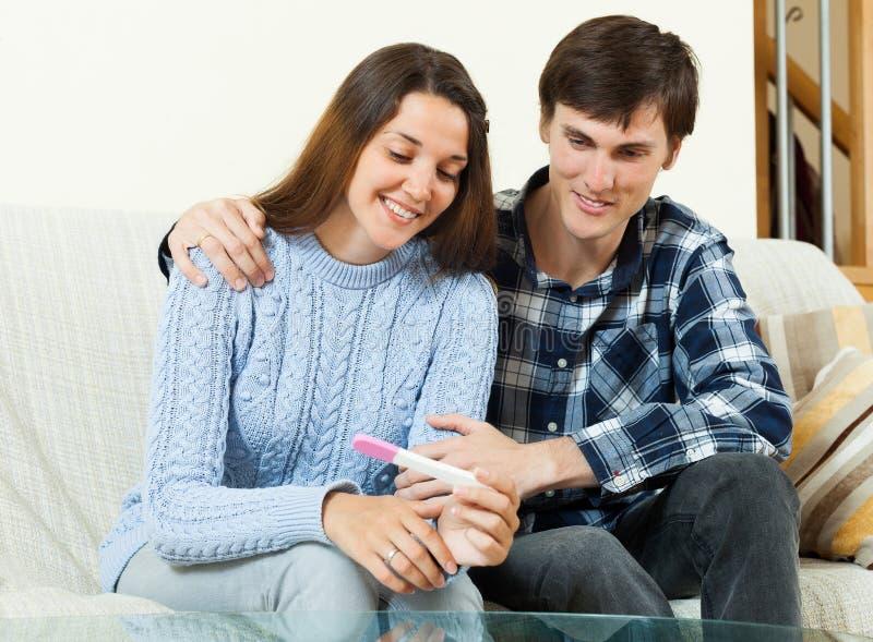Lächelnde Paare mit Schwangerschaftstest lizenzfreie stockbilder