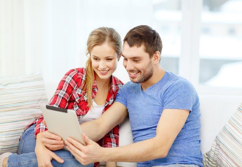 Lächelnde Paare mit Tabletten-PC-Computer zu Hause stockfotos
