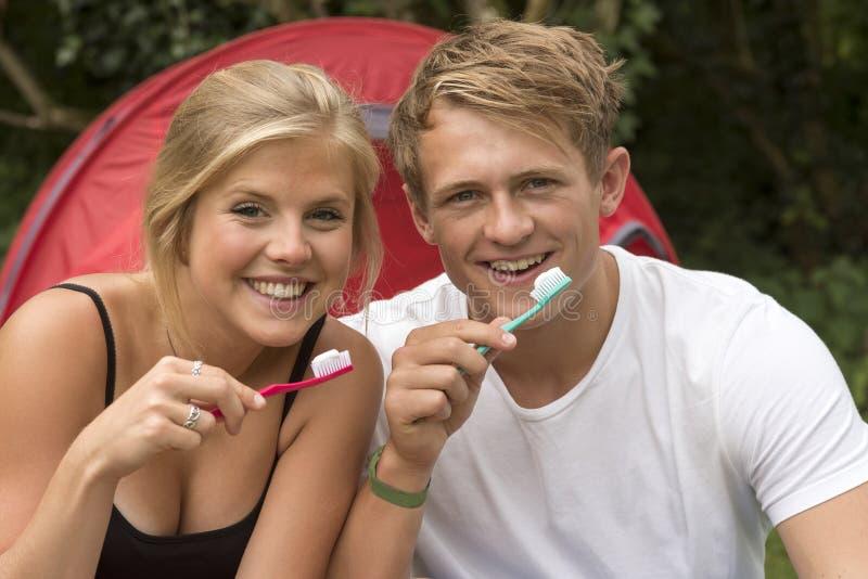 Lächelnde Paare mit Zahnbürsten lizenzfreie stockfotos