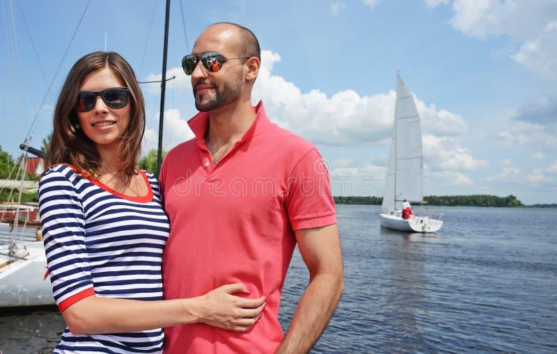 Lächelnde Paare nahe Wasser im Hafen stockbild