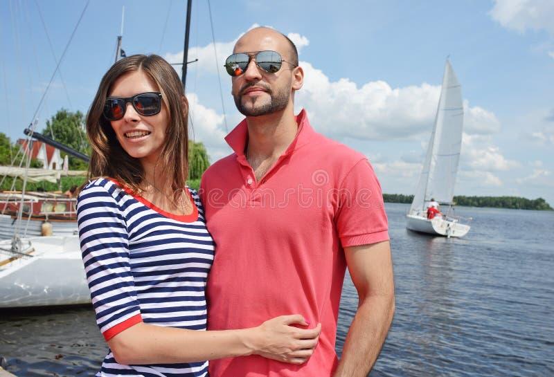 Lächelnde Paare nahe Wasser im Hafen stockfotografie