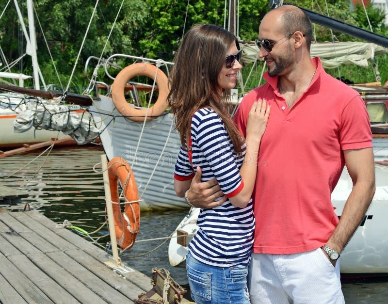 Lächelnde Paare nahe Wasser im Hafen lizenzfreies stockbild