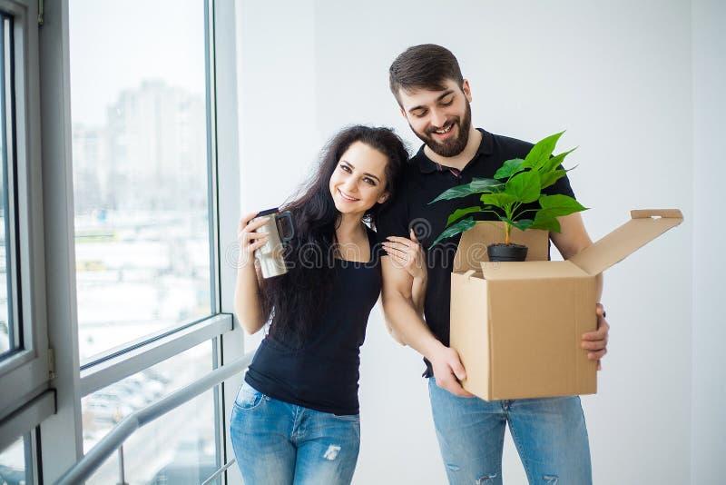 Lächelnde Paare packen Kästen im neuen Haus aus stockfoto