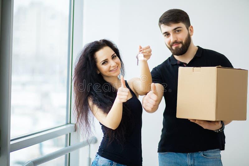 Lächelnde Paare packen Kästen im neuen Haus aus stockfotografie