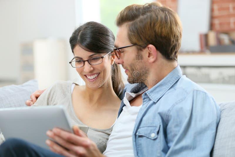 Lächelnde Paare zu Hause unter Verwendung der Tablette lizenzfreies stockbild