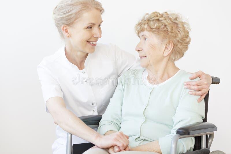 Lächelnde Pflegekraft, die ältere Frau umarmt lizenzfreie stockbilder
