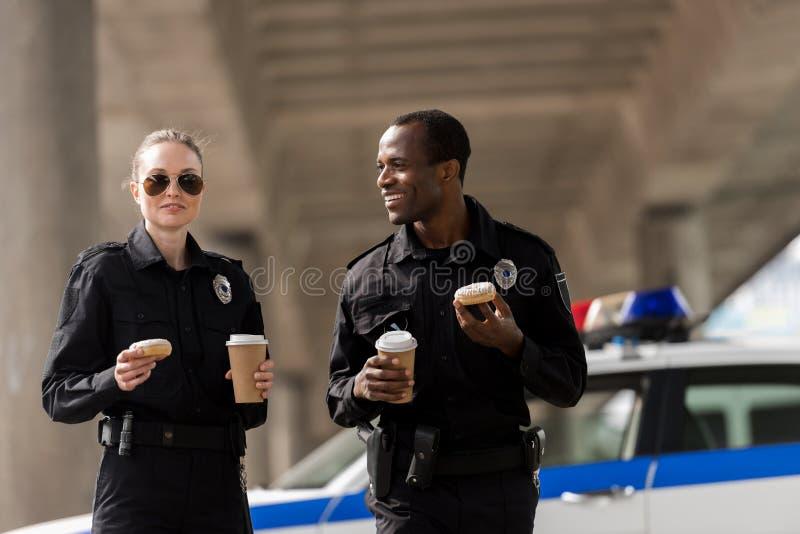 lächelnde Polizeibeamten, die Kaffeepause haben stockfotos