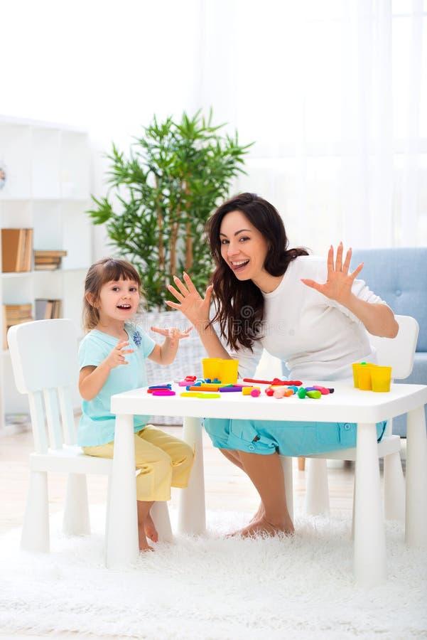 Lächelnde positive Mutter und wenig Tochter sculpt neues Haus von Plasticine Entwicklung des Kindes und Bildung Familienfreizeit  stockbilder