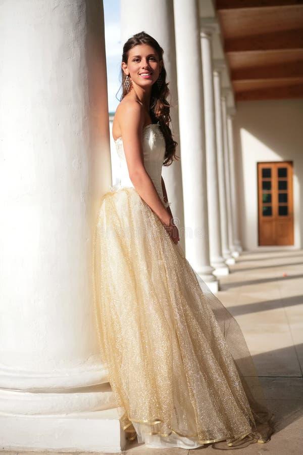 Lächelnde Prinzessin im weiß-goldenen Kleid in der Galerie lizenzfreie stockbilder