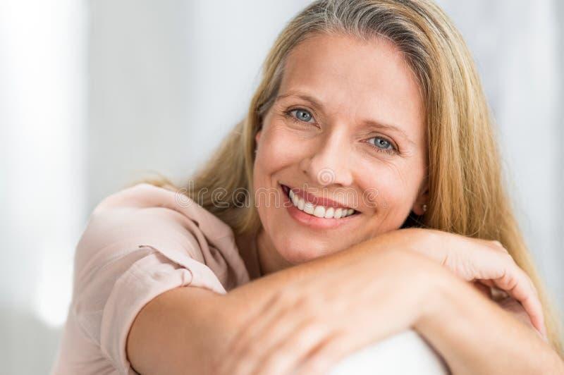Lächelnde reife Frau auf Couch lizenzfreie stockbilder