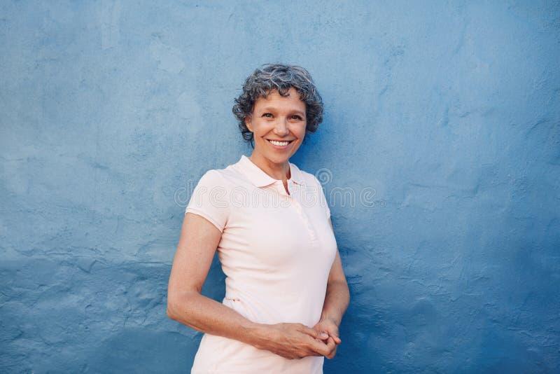 Lächelnde reife Frau, die gegen blauen Hintergrund steht stockfoto