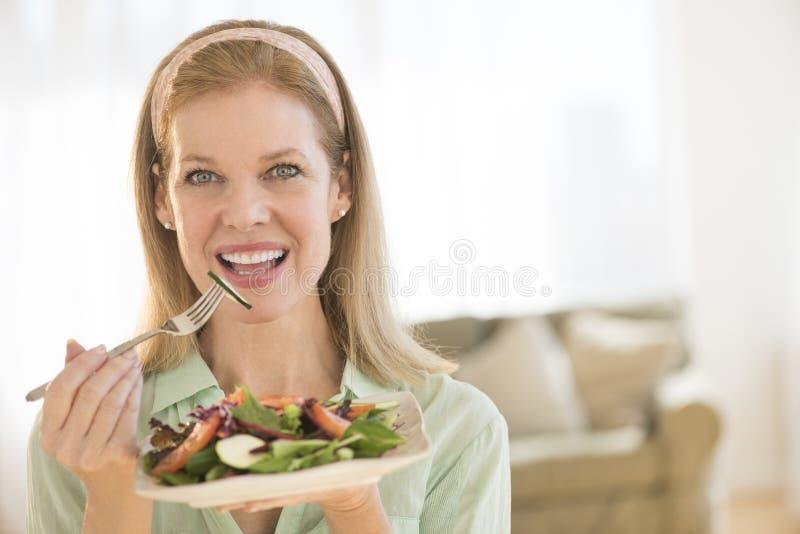 Lächelnde reife Frau, die gesunden Salat zu Hause isst stockfoto