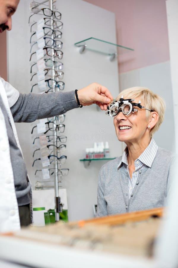 Lächelnde reife Frau, die Sehvermögenprüfung und Dioptermaß an der Augenheilkundeklinik hat stockbilder
