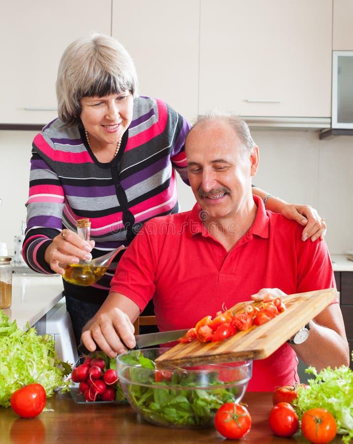 Lächelnde reife Paare, die zusammen kochen stockfotografie