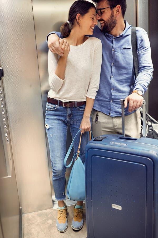 Lächelnde Reisendpaare mit Koffern im Aufzug stockbild