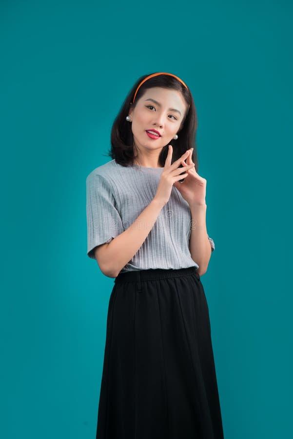 Lächelnde reizende asiatische Frau kleidete im Stift-obenartkleid über Blau an lizenzfreie stockfotografie