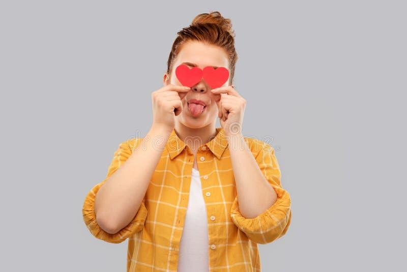 Lächelnde rote behaarte Jugendliche mit Herzen stockfoto