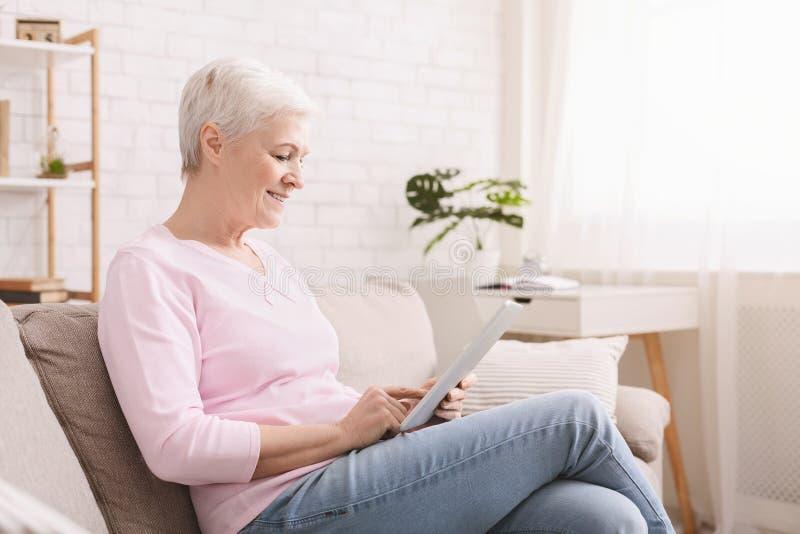 Lächelnde schöne ältere Frau, die digitale Tablette verwendet stockbilder