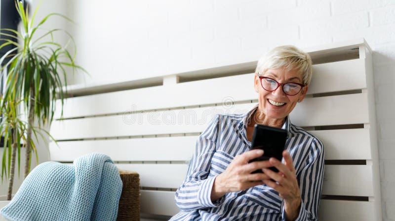 Lächelnde schöne ältere Frau, die zu Hause digitale Tablette verwendet lizenzfreie stockfotos