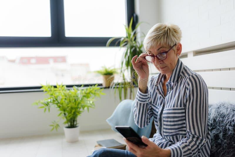Lächelnde schöne ältere Frau, die zu Hause digitale Tablette verwendet lizenzfreie stockfotografie