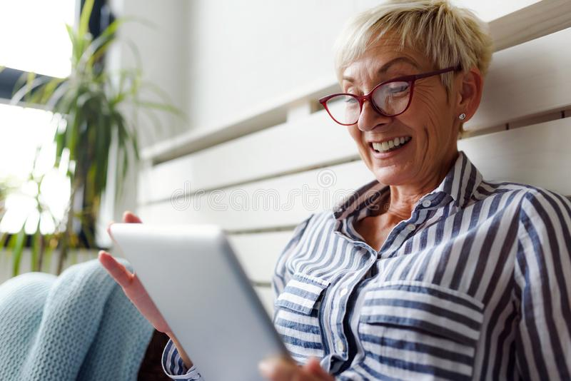 Lächelnde schöne ältere Frau, die zu Hause digitale Tablette verwendet lizenzfreies stockbild
