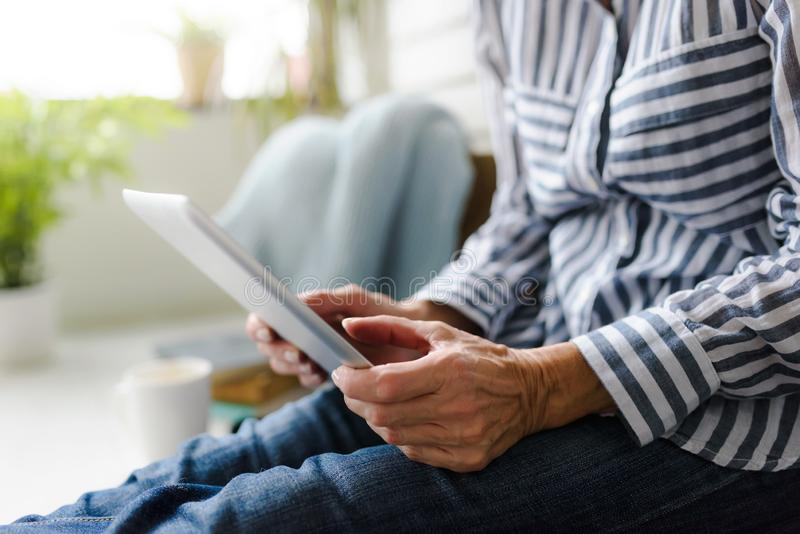 Lächelnde schöne ältere Frau, die zu Hause digitale Tablette verwendet stockfotos