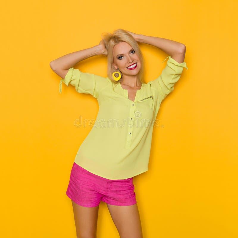 Lächelnde schöne blonde Frau hält Haupt in den Händen stockbild