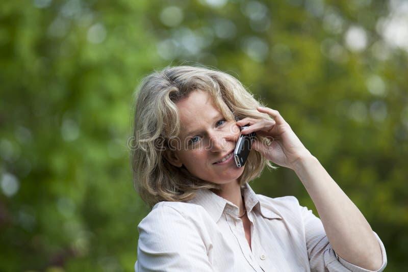 Lächelnde schöne fällige Frau mit Mobiltelefon lizenzfreie stockfotografie