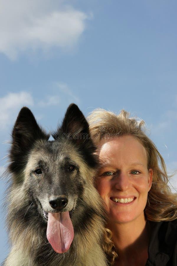 Lächelnde schöne Frau mit belgischem Schäferhund stockfoto