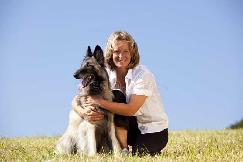 Lächelnde schöne Frau mit belgischem Schäferhund stockfotos