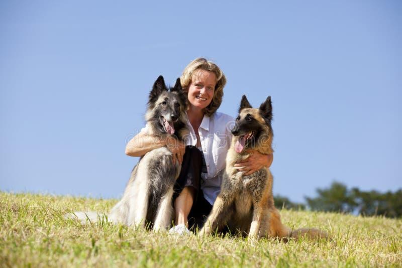 Lächelnde schöne Frau mit belgischen Schäferhunden stockbilder