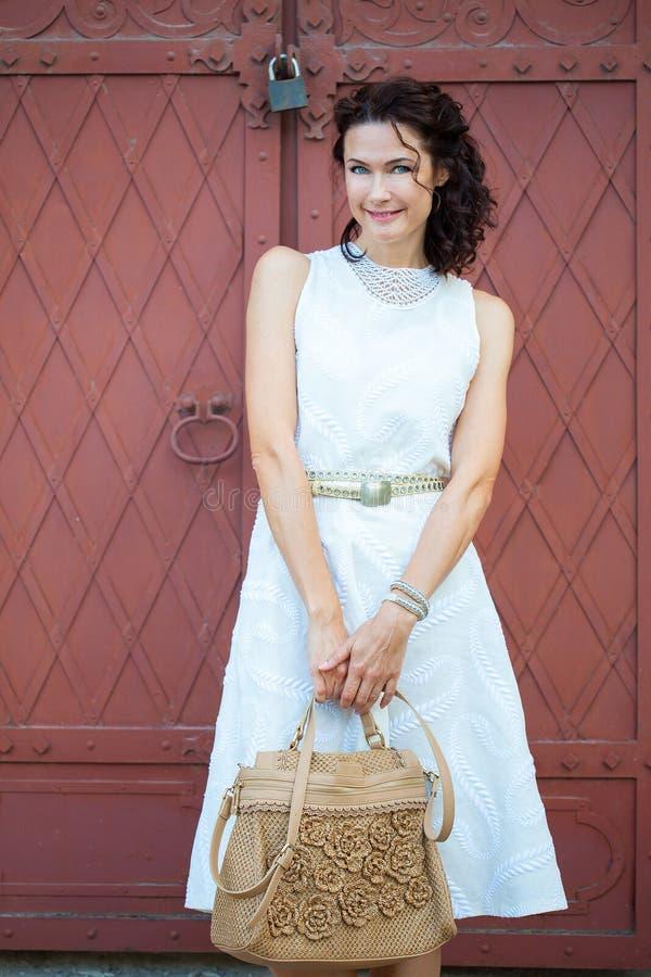 Lächelnde schöne Frau von mittlerem Alter in einem weißen Kleid stockfotos