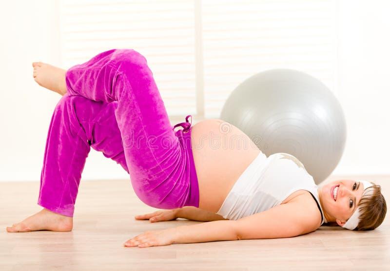 Lächelnde schöne schwangere Frau, die Übung tut lizenzfreies stockbild