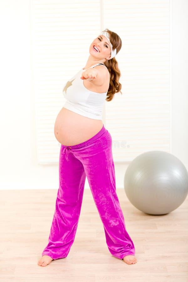Lächelnde schöne schwangere weibliche tunübung stockbild