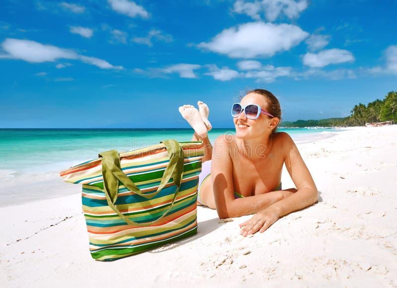 Lächelnde Schönheit, die auf einem Strand ein Sonnenbad nimmt lizenzfreie stockbilder