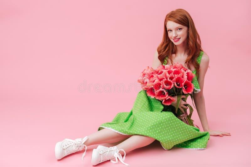 Lächelnde Schönheitsfrau, die auf Boden mit Blumenstrauß von Blumen sitzt lizenzfreies stockbild